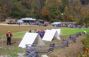 Above, Brashearsville, a salt works during the 19th century, is becoming a tourist attraction as local Civil War history hobbyists have moved log cabins from around the region to this park at Leatherwood. Close to 2,000 school kids visited the site last Friday for the living history lesson. Below, Wayne Watts of Sandlick, a retired first sergeant from the U.S. Army and a retired ROTC instructor at Letcher County Central High School, shows students how soldiers during the Civil War loaded percussion-cap muskets.