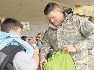 Letcher County Central JROTC Cadet Ryan Collins helps an elementary student with some items bought at the Battle of Leatherwood.