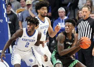 Utah Valley's Emmanuel Olojakpoke, right, looks for an opening on Kentucky's Kahlil Whitney (2) and Nick Richards (4) during the first half of an NCAA college basketball game in Lexington. (AP Photo/James Crisp)