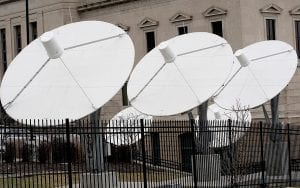 """Satellite dishes are seen on the property of KETV, an ABC-affiliated television station in Omaha, Neb. An estimated 500,000 households nationwide don't have access to local broadcast channels because of a complicated federal law and a decades-long dispute between local broadcasters and satellite television providers. Households in the nation's """"neglected markets"""" — rural areas that can't get local broadcast signals — are forced to rely on satellite service with news from other states. (AP Photo)"""