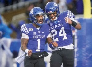 Kentucky quarterback Lynn Bowden Jr. (1) celebrated with running back Christopher Rodriguez Jr. (24) after Rodriguez scored a touchdown during the second half of the Wildcats' win against Louisville Nov. 30 in Lexington. (AP Photo/Bryan Woolston)