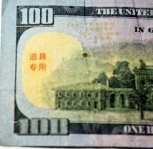 """AT RIGHT, the fake $100 bill found here last week has a series of four Chinese logosyllabic characters on the back in red ink. Translated, the symbols mean """"For Props,"""" indicating the bill might have been produced as a movie prop. (Photos by Sam Adams)"""