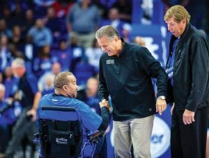 Kentucky coach John Calipari laughs as he shakes hands with Reggie Warford as former Wildcat Larry Stamper looks on. Former UK players donated $4,000 to buy a new wheelchair for Warford, who will be featured in a Christmas documentary on WKYT-TV. (Jeff Houchin Photo)
