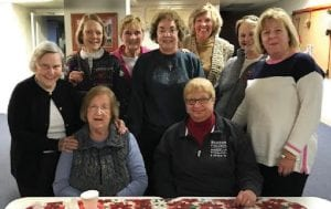 The photo above shows Letcher County native Lily Jane Collins McCraven standing center in a snapshot taken with a few of the members of a large knitting group at St. Andrew's Episcopal Church in northern Kentucky. The photo below shows Whitesburg Mayor James Wiley Craft and Letcher County Schools employee Katrina Shepherd Whisenant at a recent City of Whitesburg Christmas event as they gave away some of the dozens of scarves the knitters sent to Letcher County to be given away as presents.