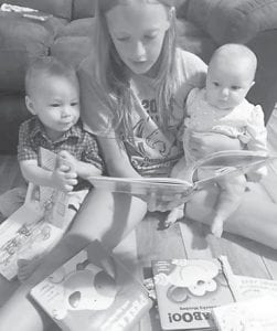 Kole and Emma Fleming, children of Dalton Fleming and Lauren Noble, enjoy a story read by their cousin Isabella Holbrook, daughter of Stephanie and Lennie Holbrook, Jr. Isabella is the granddaughter of Rotarian Lennie D. Holbrook, Sr. and Kole and Emma are his greatgrandchildren. Kole and Emma receive a free book each month from Dolly Parton's Imagination Library Program and will continue to receive a free book each month until they turn five.