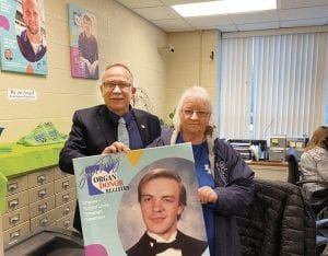 """ORGAN DONOR HERO — Letcher Circuit Court Clerk Mike Watts and Ellen Addington, of Jenkins, hold a large image of Mrs. Addington's late son, Eric Shawn Addington, whose organs were donated after he was killed in a traffic accident in 1997. The image has been added """"Our Heroes"""" wall in the clerk's office."""