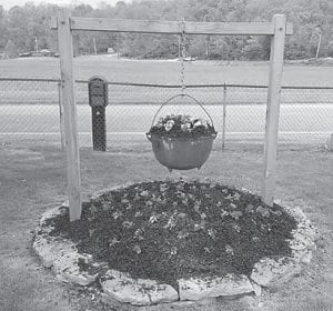 """Rose Ballard says, """"My son Keith Ballard made this for Mother's Day. The iron pot is over 100 years old, and it was given to me. The pot didn't have a bail, somehow how Keith used a torch to make the bail from an iron rod. The dirt is in a mound. Keith put a lot of thinking and effort in doing this for me."""""""