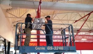 INVESTING IN SAVINGS — County Recreation Director Jeremiah Johnston (left) and Deputy Judge Jason Back removed fluorescent bulbs from a fixture in the gymnasium ceiling at the Letcher County Recreation Center to make room for LEDs.