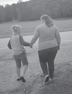 Rose Ballard's granddaughter Jessica Nottingham holds her hand to steady her as they were walking through the yard on her 75th birthday.