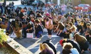 NINE MINUTES OF SILENCE – Protesters knelt in front of Whitesburg City Hall for eight minutes and 46 seconds in memory of George Floyd, who was killed by a police officer kneeling on his neck. They were participating in a peaceful protest in Whitesburg on Friday evening remembering Floyd and Breonna Taylor, who was killed by police in Louisville in March. (Photo by Sam Adams)