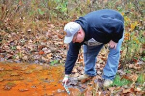 Dustin White of the Ohio Valley Environmental Coalition tests the quality of water in a stream that's tainted orange from acid mine drainage in southern West Virginia. (Photo by Mark Olalde, DeSmog.)
