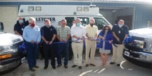 """MOVING AHEAD — Members of Letcher Fire and Rescue and local and state officials gathered to cut the ribbon on the department's new Advanced Life Support service, and its newly remodeled station on Tuesday. Pictured (left to right) are Director of Patient Services Jai Miller (rear), board chairman Paul Radosevich, Fire Chief Wallace """"Spanky"""" Bolling, EMT Joseph Elish (rear), Letcher County Judge/Executive Terry Adams, Director of Human Resources Keith Smith (rear), Executive Director Shawn Gilley, 29th District State Sen. Johnny Ray Turner, 94th District State Rep. Angie Hatton, and Director of Paramedicine Chris Gilley. (Photo by Sam Adams)"""