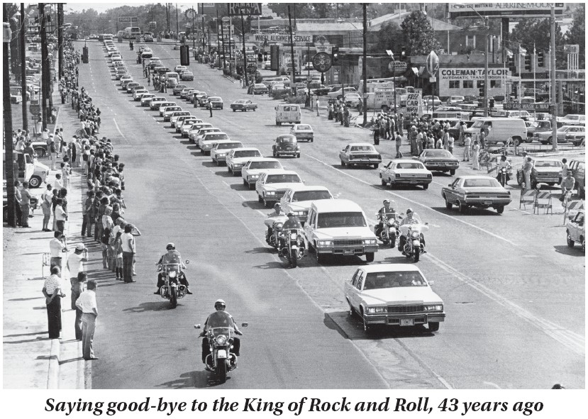 A string of white vehicles followed the hearse carrying the body of rock and roll musician Elvis Presley along Elvis Presley Boulevard on the way to Forest Hills Cemetery in Memphis, Tenn., August 19, 1977. Thousands of people lined the route for the city's final tribute to Elvis. Presley died suddenly August 16, 1977 at his Graceland estate in Memphis. He was 42. (AP Photo)