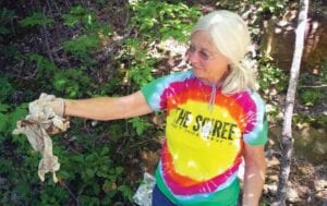 Katy Eagle holds handful of latex gloves found dumped on her property beside Little Shepherd Trail. She blames someone attending or working with the rally, and says she opposes using the trail as a racetrack. (Photo by Sam Adams)