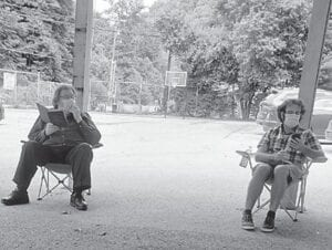 Seated six feet apart are John Pickow (left) and Ben Fink.