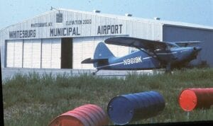 """OLD WHITESBURG MUNICIPAL AIRPORT – This photo taken August 29, 1969, by Linc Reed-Nickerson shows his 1947 Stinson Voyager in front of the Whitesburg hangar. Reed-Nickerson landed there after learning the Bluefield, W.Va., airport was fogged in. This photo appears on the website """"Abandoned and Little Known Airfields: Eastern Kentucky."""""""