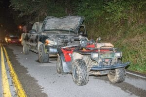 A pickup truck sits against the rear end of a four-wheeler after a crash Friday on KY 805 in Jenkins. The riders of the four-wheeler were injured — one critically — and the driver of the truck, Darrell Wyatt of Jenkins, was charged with driving on a license already suspended for DUI. (Photo by Chris Anderson)