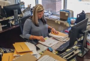 ABSENTEE BALLOTS WILL be in the mail this week to those who have already ordered them on the state portal. Pictured, Sharaye Whitaker prepares ballots for mailing in the Letcher County Clerk's Office on Tuesday. (Photo by Sam Adams)