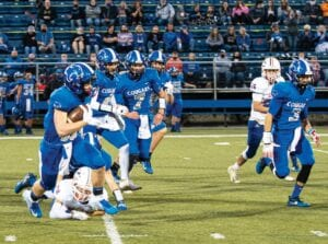 Running back Isaac Matthews breaks free from an attempted tackle and carries the ball upfield with blocking assistance from LCC teammates, left to right, Kaden Barnette, Reece Barnette, Jonah Little, Luke Goins and Trevor Branham in the Cougars' walloping of Pike Central last Friday.