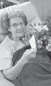 Dorothy Tacket holds flowers from her granddaughter Ashley Tacket Ellis and grandson A.J. Tacket.