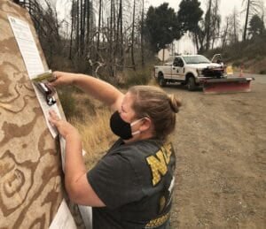 WILDFIRE FIGHTER Hannah Thompson-Welch places burn notices on a bulletin board as part of her job preventing forest fires. A native of Hemphill, she now works in North Carolina and travels to wildfires across the country when needed.