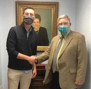 Dr. Colton (Cole) Cornett, left, shook hands with Mountain Comprehensive Health Corporation CEO L.M. (Mike) Caudill after Dr. Cornett agreed to return to Letcher County to practice pediatrics.