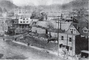 THE WAY WE WERE AND ARE – These pictures of Whitesburg's East Main Street (formerly Railroad Street) depict the east end of downtown as it was a century ago and today. At top, the streets of Whitesburg — first paved in 1924 — were still dirt when this picture was taken. In the background, far away and on the left of Main Street, is the Daniel Boone Hotel, on which construction began in 1919, and which opened Independence Day weekend of 1920. In the foreground is a building that appears to be the same one one that is still standing and was later used as Clara's Diner, Carolyn's Diner, Ramey's Diner and the Railroad Street Merchantile. The L&N Railroad rails can be seen in the bottom edge of the photo.