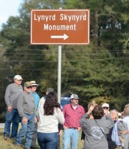 Fans and monument organizers gathered last week at newly dedicated highway signs for the Lynyrd Skynyrd Monument near the site of the band's October 20, 1977, plane crash in Gillsburg, Miss. (Matt Williamson/The Enterprise-Journal via AP)