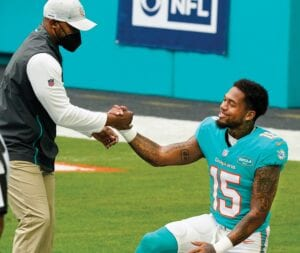 A rash of Miami Dolphins injuries has given rookie receiver Lynn Bowden Jr. the chance he never had with the team that drafted him. With Miami's top four receivers sidelined by the end of Sunday's game against Kansas City, Bowden, pictured with Dolphins head coach Brian Flores, was busy. He had seven catches for 82 yards, both season highs that led the team. (AP Photo)