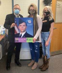 NEW HERO – Letcher Circuit Clerk Mike Watts displays a photo of Airman Ethan W. Potter with Potter's mother, Kimberly Hale, and his sister Nakeia Potter. Potter's portrait will hang on the clerk's office wall with other organ donors.