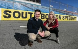 Letcher County native Chase Brashears and his wife Carly pose on the asphalt racing track at South Boston Speedway in Halifax County, Virginia. Mr. Brashears, a graduate of Letcher County Central High School, will serve as assistant general manager through the 2021 season, and will become the speedway's general manager in 2022. Mrs. Brashears will work as the speedway's assistant office manager during 2021, and will handle the track's marketing, sales and administrative functions during the 2022 season.