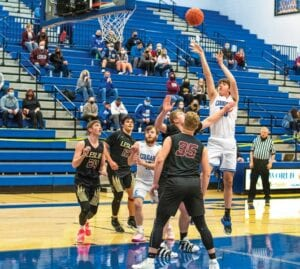 Below, Kaden Adams shoots a short jumper, scoring two of his nine points in the Cougars' 65-51 win over Leslie County at home last week.