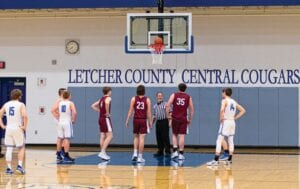 """STUCK IN PLACE — Play was stopped during the Letcher County Central boys' matchup against visiting Knott Central last week after an errant shot stuck on the rim. Play was stopped and the ball was knocked off the rim. The ruling by the game's officials was a """"jump ball."""" The Cougars lost, 72-52. (Photo by Chris Anderson)"""