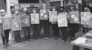 Ladies hold their daisy paintings from the Monday night class held at Mountain of Scraps.