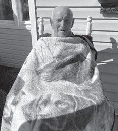 Johnny Calihan enjoys the sunshine on their porch, proof of God answering prayers. You can't keep a good man down.