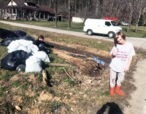 Elizabeth Jones and her two sons, Gregory, 10, and Allan, 9, cleaned up this garbage pile left byfloodwaters recently near their home at Grays Branch, Potters Fork.
