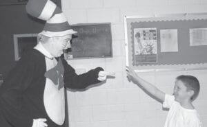 """Billy Keith Adams was pleasing elementary school students by dressing up as """"The Cat in the Hat"""" when he was still a hairdresser in this 2011 photo with student Landon Tolliver at West Whitesburg Elementary."""