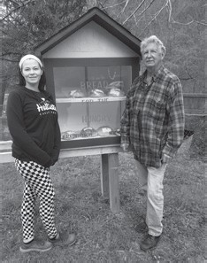 Mary Grace Sturgill, one of the bakers, and carpenter Richard Stewart pose with the newly installed insulated bread shed located at Hemphill Community Center.