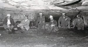 WHEN HE WAS A YOUNG PRACTICING ATTORNEY, Whitesburg Mayor James Wiley Craft (far left) visited with coal miners inside the old South- East Coal Company underground mine at Polly. This photo was taken by Bill Richardson after Craft won a case for South-East and the miners.