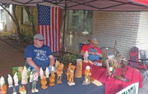Maurice Vanhook and Shawn Eldridge, both members of Mountain Tradition Carving, whittled wood figurines under a canopy in Big Stone Gap recently.